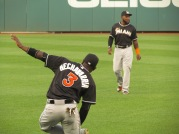 Adeiny Hechavarria stretches before the game as Marcell Ozuna lurks in the distance